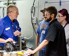 Instructor working on HVAC with students.