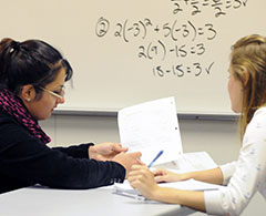 Instructor helping student with math equations.