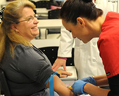 Phlebotomist drawing patient's blood.